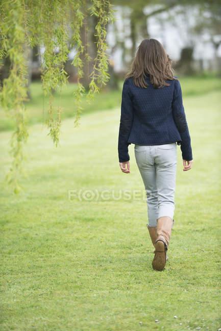 Vista traseira da menina andando no campo verde — Fotografia de Stock
