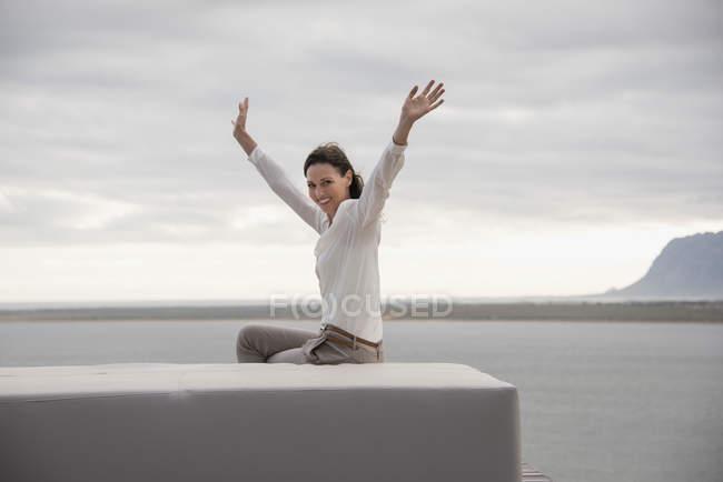 Portrait de femme heureuse assise sur ottoman avec les bras levés au bord du lac — Photo de stock