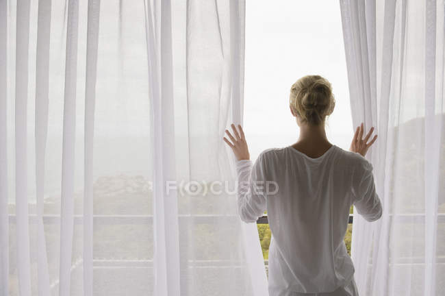 Rear view of woman opening curtain of balcony at home — Stock Photo