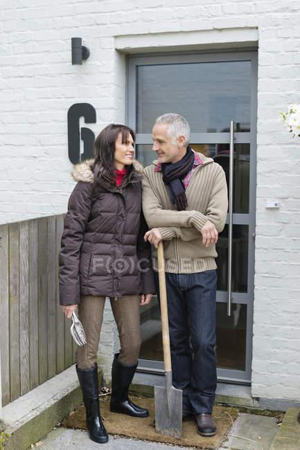 Ehepaar steht mit Schaufel vor Wohnungstür — Stockfoto