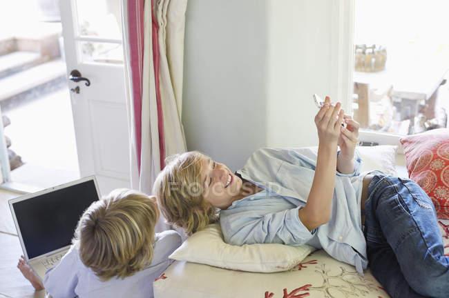 Bambini che utilizzano gadget elettronici a casa — Foto stock