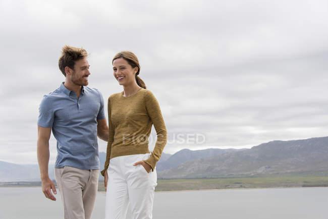 Young smiling couple having fun at lake shore — Stock Photo