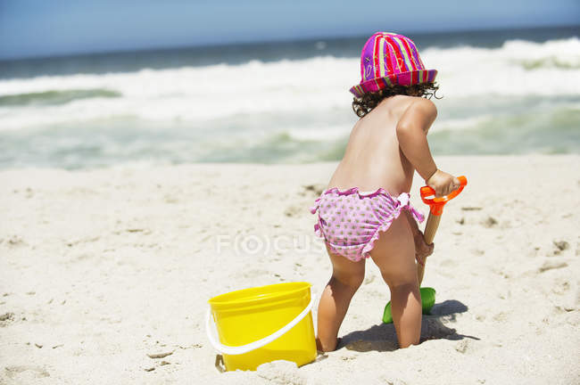Rear view of little girl digging with sand shovel on beach — Stock Photo