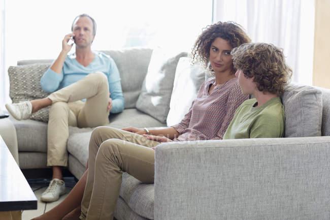 Madre hablando con el hijo en el sofá mientras padre hablando por teléfono en el fondo en la sala de estar en casa - foto de stock