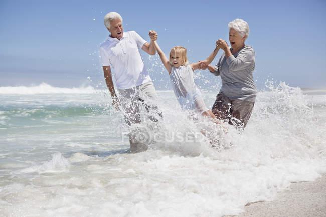 Fille ayant l'amusement sur la plage de mer avec des grands-parents — Photo de stock