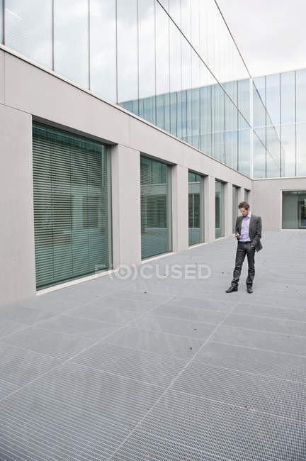 Businessman text messaging on mobile phone outdoors office building — Stock Photo