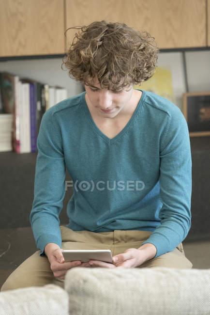 Adolescente ragazzo utilizzando tablet digitale in soggiorno — Foto stock