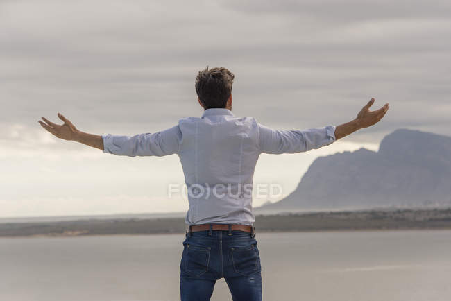 Rear view of man standing at lake shore with arms outstretched — Stock Photo