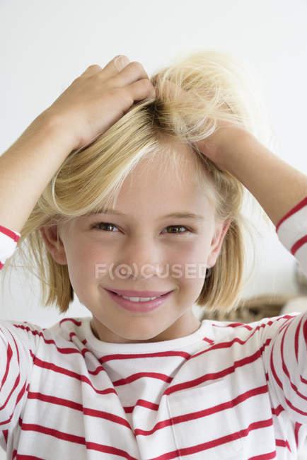 Ritratto di bambina felice che tocca i capelli biondi — Foto stock