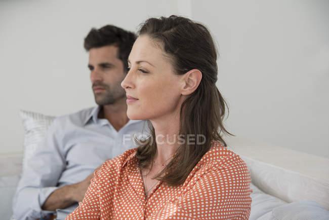 Nahaufnahme einer nachdenklichen Frau auf dem Sofa sitzend mit Ehemann im Hintergrund — Stockfoto