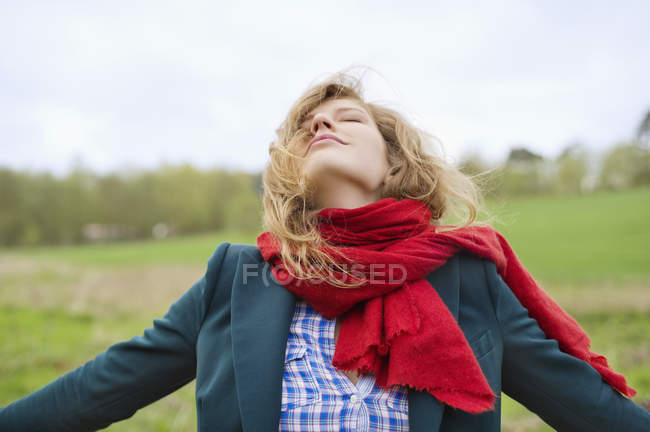 Young woman in red scarf with eyes closed daydreaming in field — Stock Photo