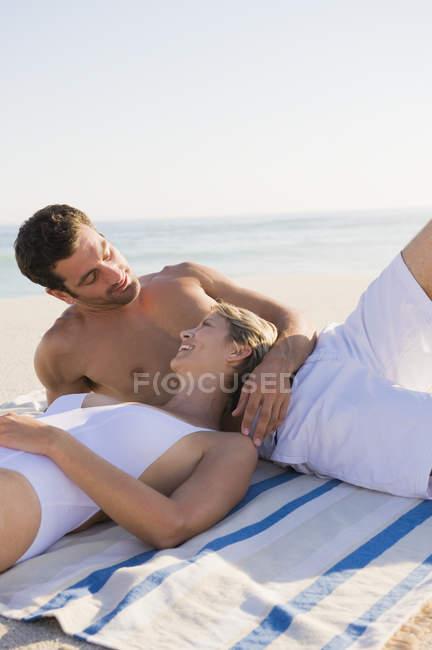 Coppie Relaxed che ride, che riposa sulla spiaggia sabbiosa — Foto stock