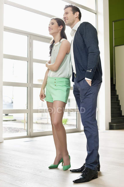 Smiling young couple looking around in new house — Stock Photo