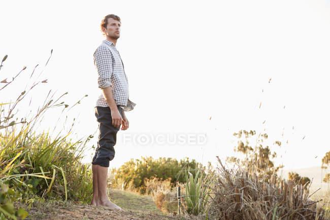 L'uomo in piedi sul sentiero nella natura e guardando lontano — Foto stock