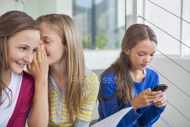 Estudantes do sexo feminino fofocando enquanto menina solitária usando telefone celular na escola — Fotografia de Stock