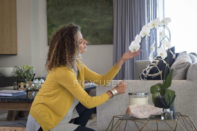 Продуманий жінка, торкаючись квітки орхідеї в домашніх умовах — стокове фото