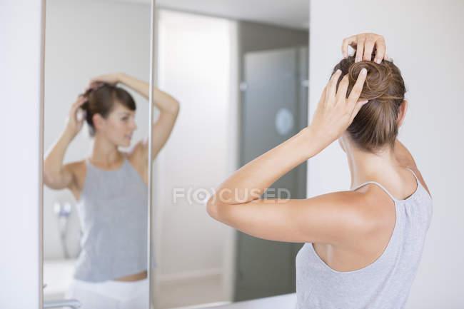 Mujer joven ajustando el pelo delante del espejo en el baño - foto de stock