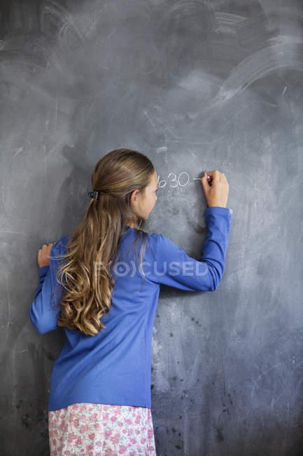 Primo piano di una ragazza che scrive sulla lavagna in classe — Foto stock