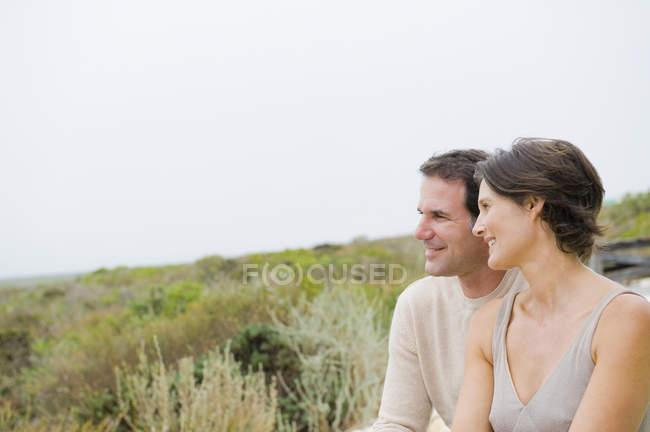 Feliz pareja sentados juntos en la naturaleza y al mirar ve - foto de stock
