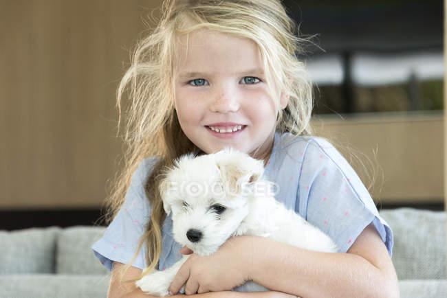 Portrait de mignonne petite fille tenant chiot — Photo de stock