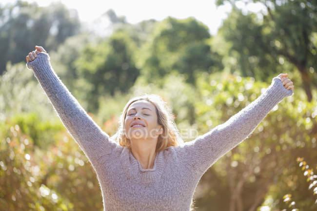 Щасливі жінка з руки розкритими і очі закриті стоячи в саду — стокове фото