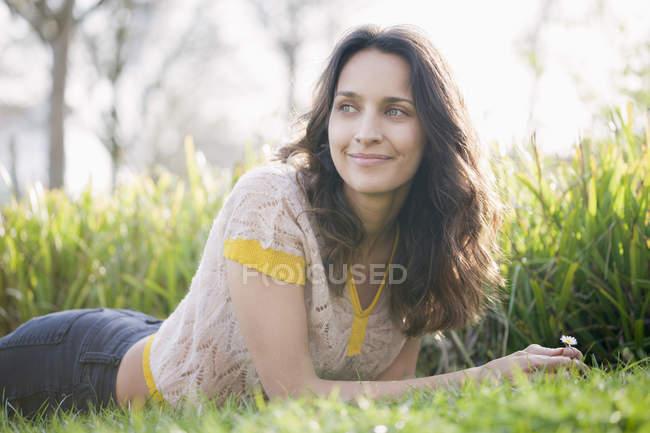 Glückliche, lässige Frau liegt im Gras in sonniger Natur — Stockfoto