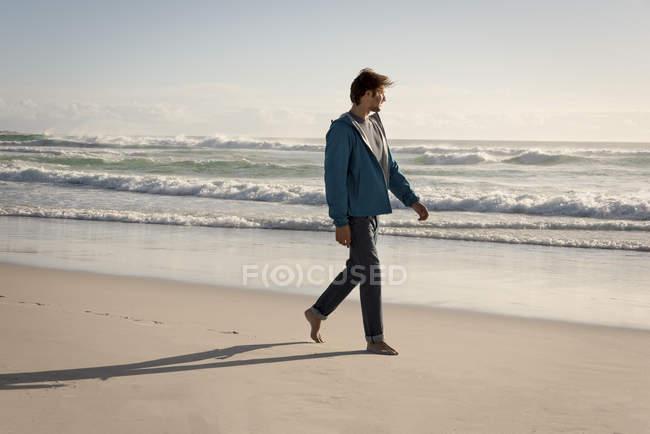 Happy young man walking on sandy beach — Stock Photo