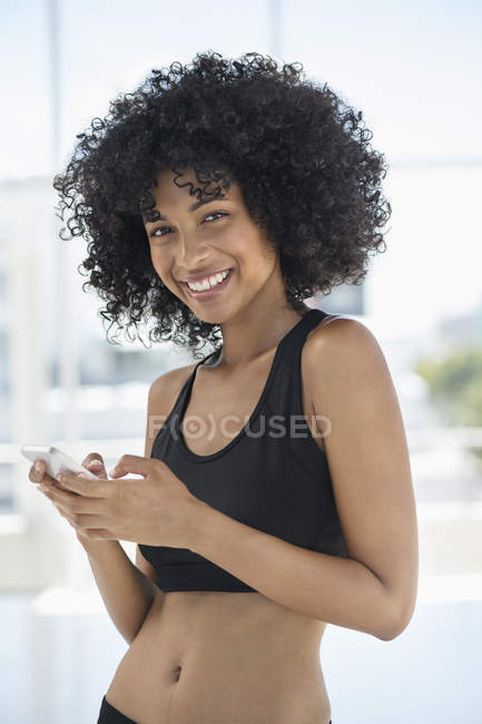 Portrait of smiling sport woman using mobile phone — Stock Photo