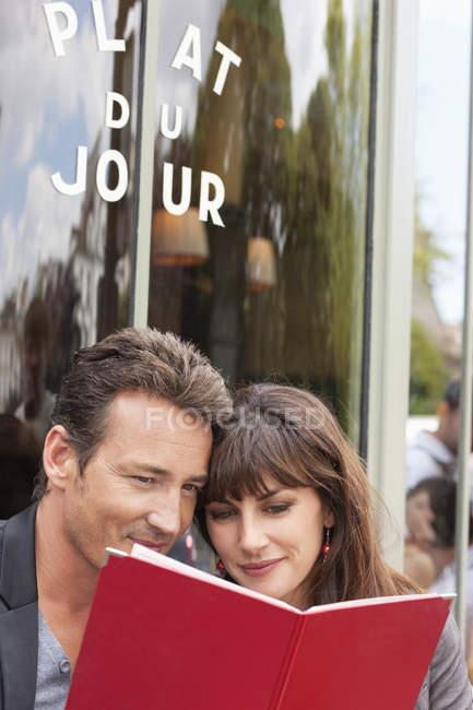 Romantique couple lecture menu au restaurant de rue — Photo de stock