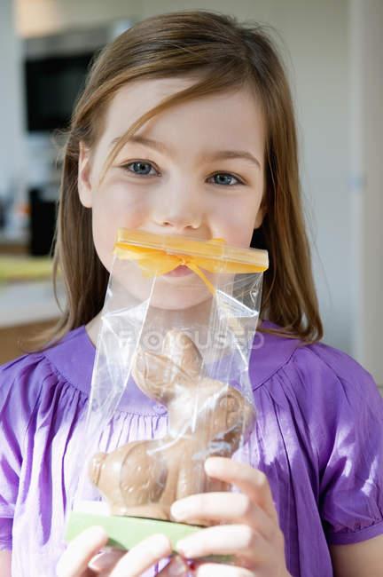 Портрет маленькой девочки, держащей пасхального кролика перед лицом — стоковое фото