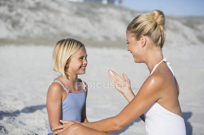 Smiling mother and daughter looking at each other on beach — Stock Photo