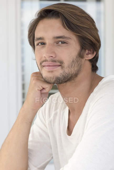 Portrait of smiling young man sitting and leaning on elbow — Stockfoto