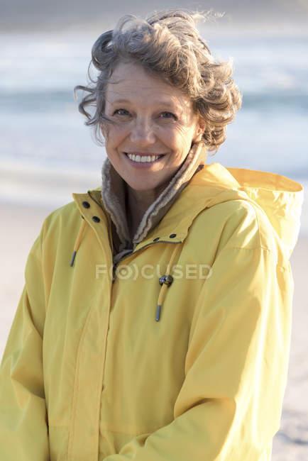Retrato de mujer madura feliz en impermeable de pie en la playa - foto de stock