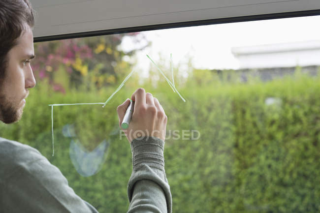 Closeup of man drawing architecture design on glass of window — Stock Photo