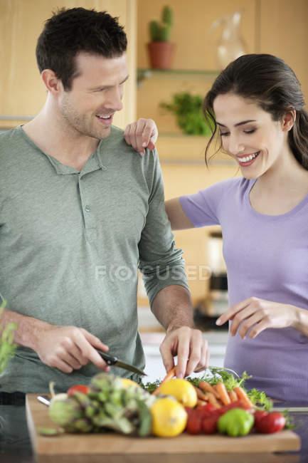 Happy couple cuisine dans la cuisine ensemble — Photo de stock