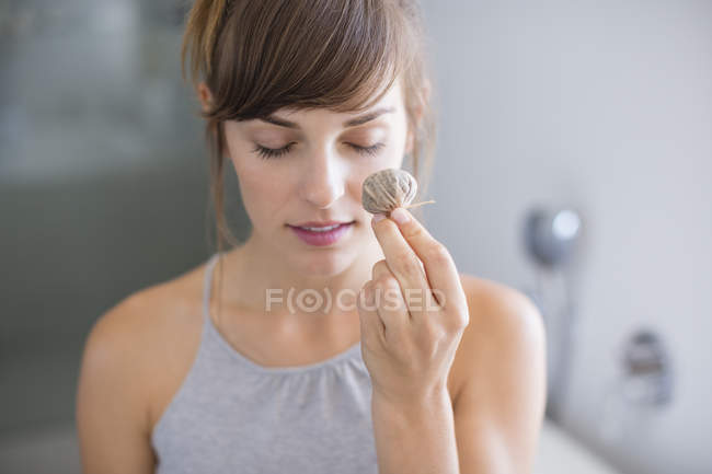 Close-up of young woman smelling tea bag — Stock Photo