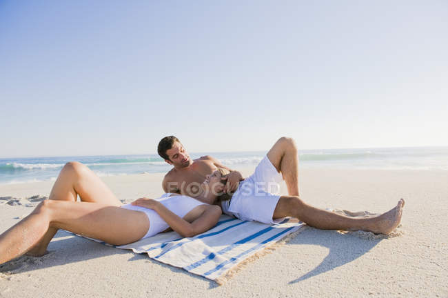 Relaxed laughing couple resting on sandy beach — Stock Photo