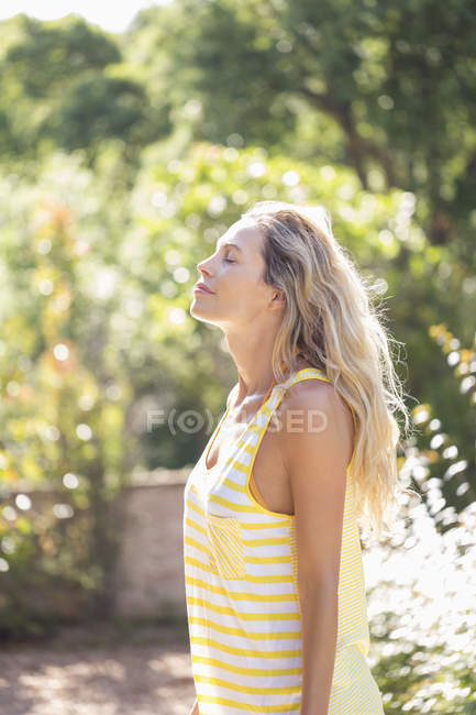 Relaxed woman with eyes closed standing in park — Stock Photo