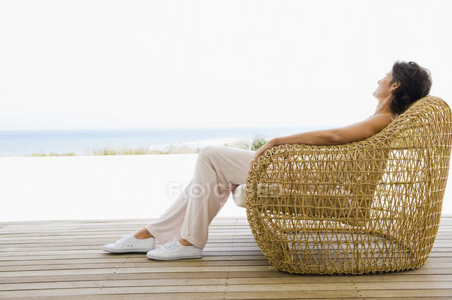 Woman reclining on wicker chair on terrace on coast — Stock Photo