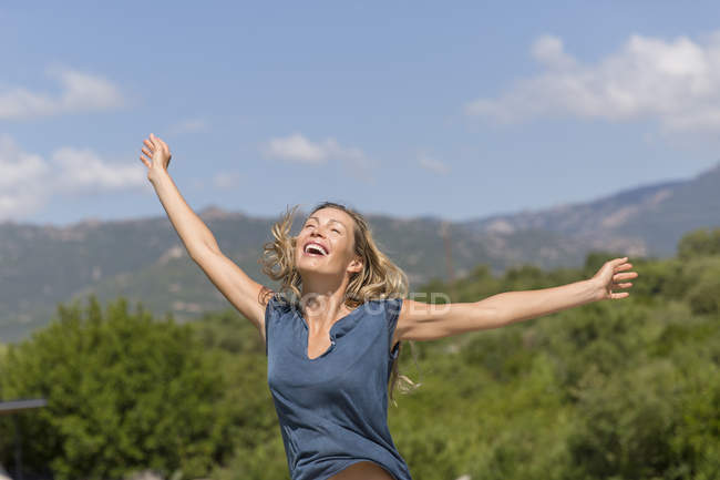 Happy woman with arms outstretched standing in mountains — Stock Photo