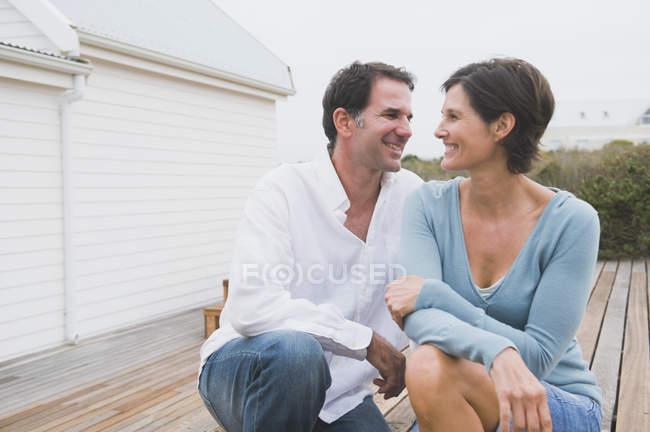 Paar lächelt gemeinsam vor Haus an der Küste — Stockfoto