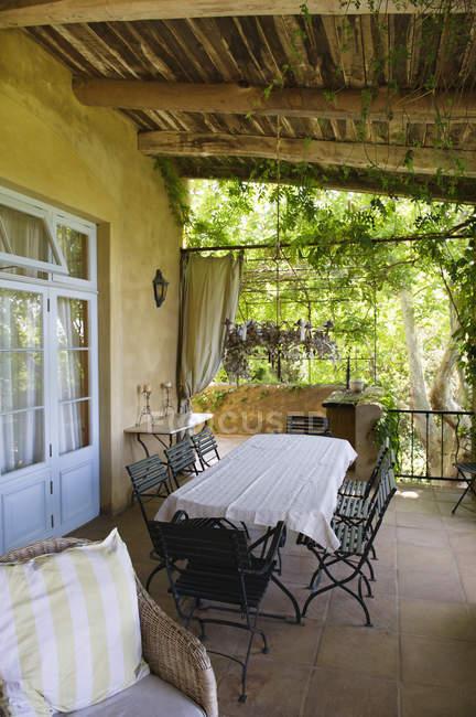 Mesa e cadeiras na varanda da casa rural no verão — Fotografia de Stock