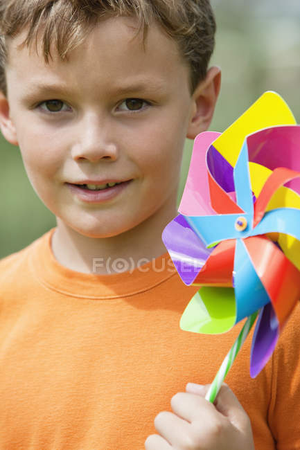 Portrait of little boy holding colorful pinwheel outdoors — Stock Photo