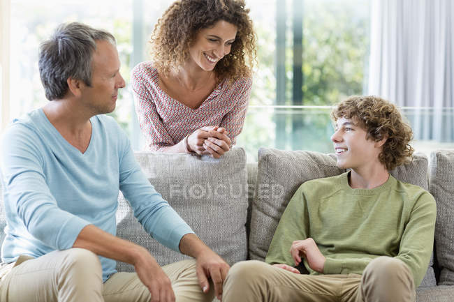 Famiglia felice che sorride nel salotto a casa — Foto stock