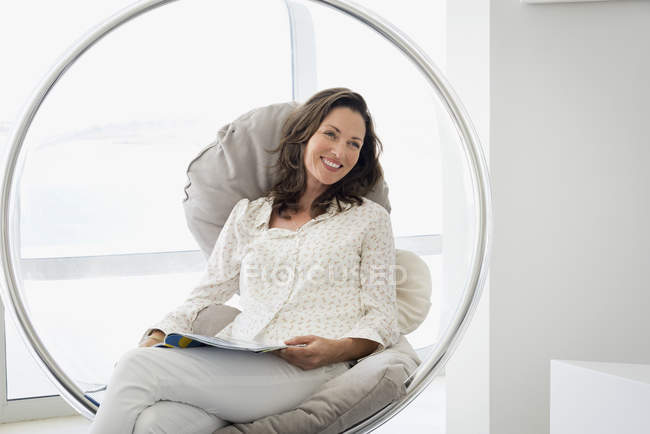 Happy mature woman relaxing in chair with magazine — Stock Photo