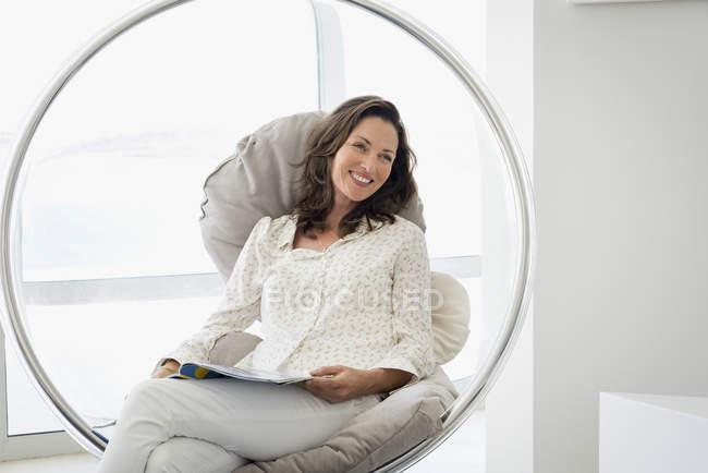 Feliz relaxante na cadeira com revista de mulher madura — Fotografia de Stock