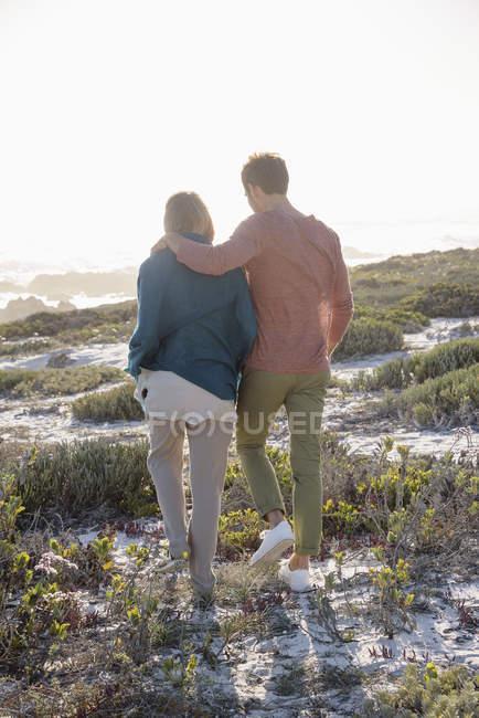 Романтическая пара, гуляющая по побережью с растительностью под солнечным светом — стоковое фото