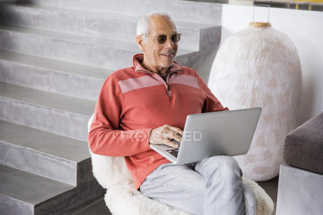 Happy senior man using laptop in armchair — Stock Photo