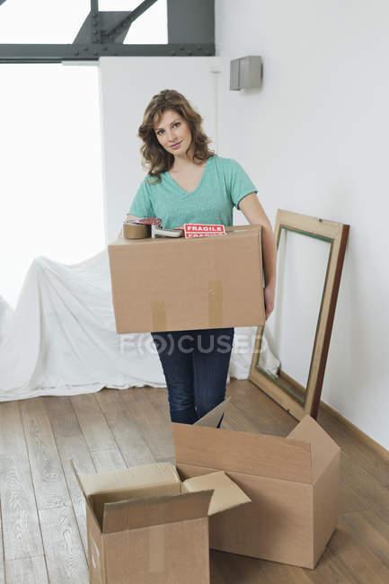 Femme portant des cartons boîtes en appartement — Photo de stock