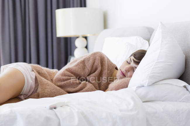 Young woman in comfy sweater sleeping on bed — Stock Photo